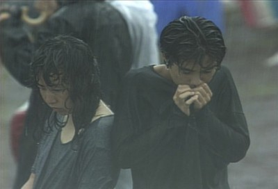 大雨に打たれ放心状態のカッップル。客席はどこもかしこも水浸しとなり悲惨な状態のなかライブは続いた。